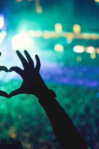 Hands forming a heart at concert